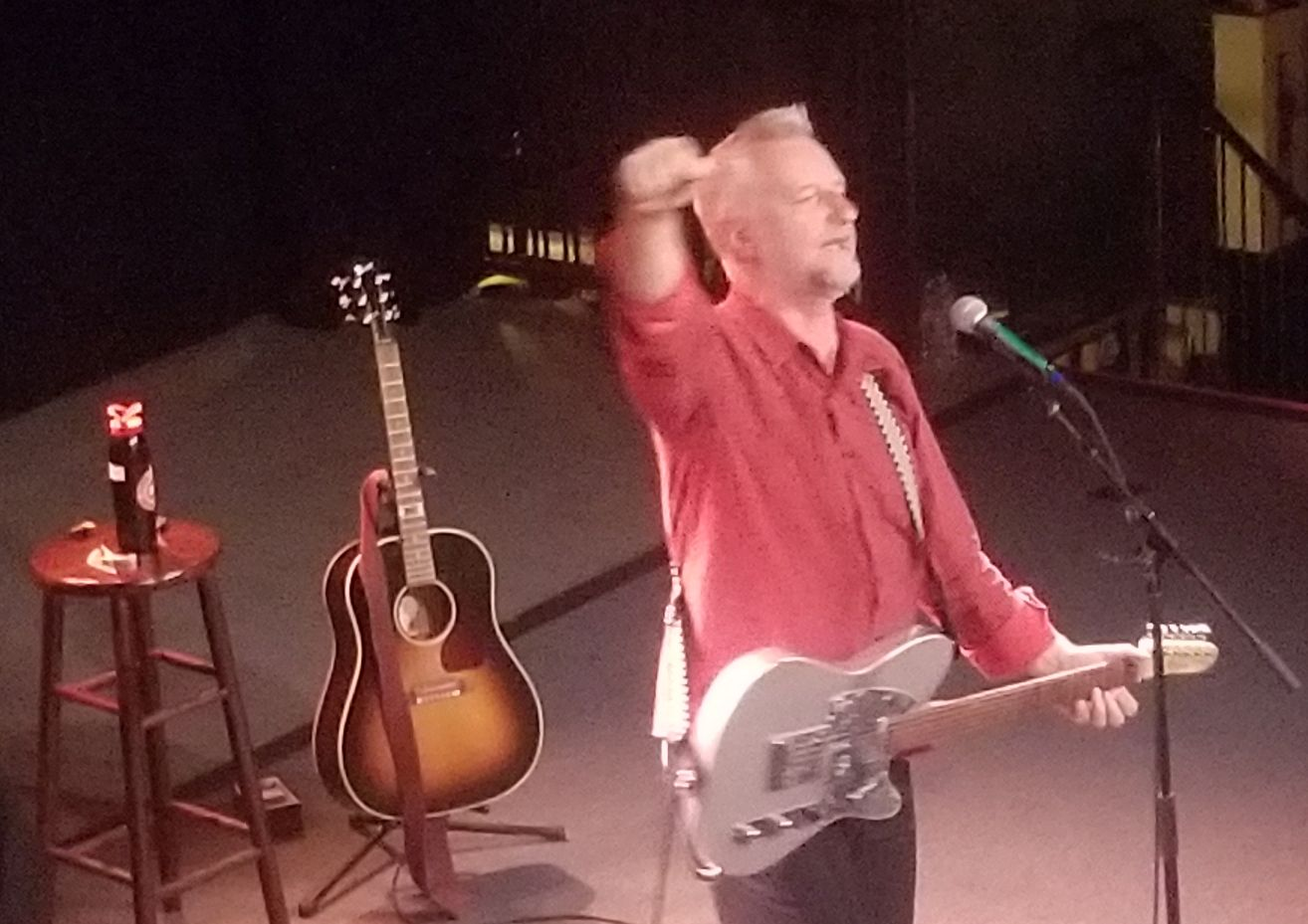 Billy Bragg at the Sinclair 10 3 2019 with Billy holding his fist in the air and singing into a microphone